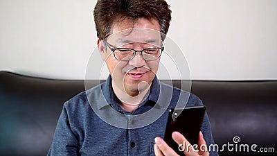 Homem asiático de meia-idade a ter uma vídeo-chamada feliz usando um smartphone vídeos de arquivo