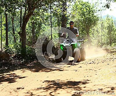 Homem asiático que conduz o veículo todo-terreno na selva