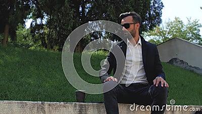 Homem atrativo com barba de terno clássico põe óculos de sol, depois bebe chá ou café de uma xícara descartável 4 k vídeo 4k vídeos de arquivo