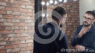 Homem barbudo que procura iluminar o espelho antes de sair do apartamento Homem bonito com barba e óculos olhando para espelho vídeos de arquivo