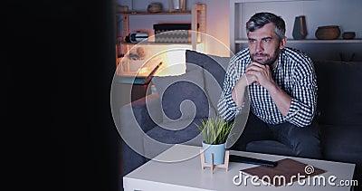 Homem barbudo sério assistindo TV à noite em apartamento escuro sentado no sofá video estoque