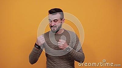 Homem bonito olhando para a câmera, mantendo os punhos levantados, lutando, gesto vencedor video estoque