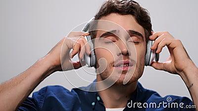 Homem bonito ouvindo música nos fones de ouvido O cara que gosta de música nos fones de ouvido vídeos de arquivo