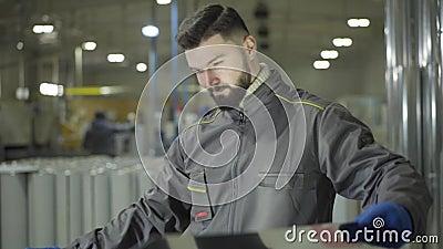 Homem caucasiano cardado em luvas de trabalho em pé em tubos metálicos de aço que seguram chapa metálica Verificação de jovens tr video estoque