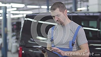 Homem caucasiano jovem e bonito de roupa de trabalho, de pé com tablet no fundo do carro preto Mecânico automóvel masculino grave filme