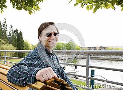 Homem caucasiano nos anos quarenta que sentam-se no banco pelo lago