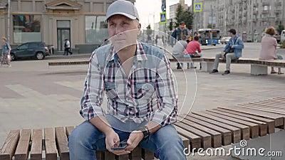 Homem caucasiano sentado no banco da cidade quadrada segurando smartphone olhando à frente filme