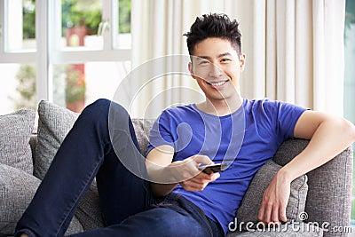 Homem chinês novo que presta atenção à tevê no sofá em casa
