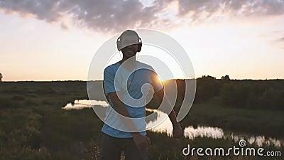 Homem com auscultadores faz dança popular no pôr do sol em câmera lenta filme