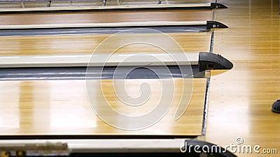 Homem com a bola que joga o boliches em uma pista de boliches no centro de esportes media Jogue uma bola de rolamento nos pinos d filme