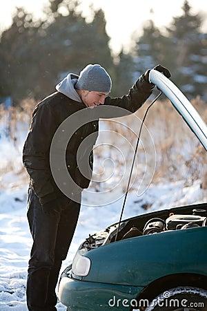 Homem com o carro quebrado no inverno