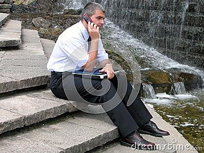 Homem com telefone e computador