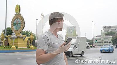Homem considerável novo do turista que usa o telefone ao esperar na rua de Ratchadamnoen em Banguecoque filme