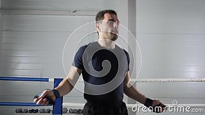 Homem de combate aquecendo com corda pulando no ringue de boxe Exercício de treinamento de atleta com corda pulante na academia video estoque