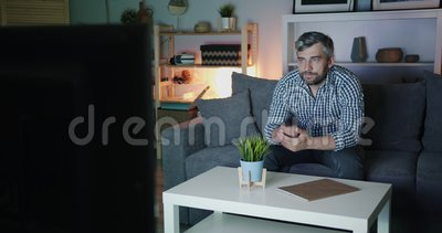 Homem de meia idade assistindo TV em casa à noite no sofá sozinho segurando um controle remoto video estoque