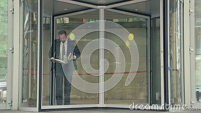 Homem de negócio com os papéis e o caderno que saem do prédio de escritórios que apressa-se e que tropeça video estoque