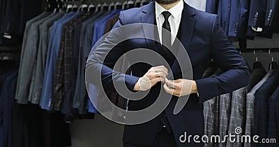 Homem de negócio elegante na camisa branca que corrige seu laço e que abotoa seu revestimento do terno Fim acima filme