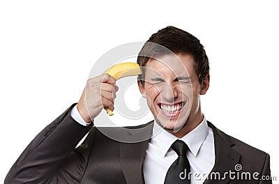 Homem de negócio que gesticula o injetor com banana