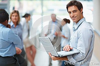 Homem de negócio que usa colegas do portátil na parte traseira