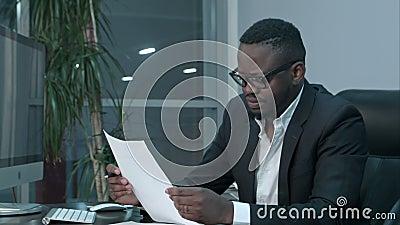 Homem de negócios africano que faz o documento, contas de finança calculadoras no escritório video estoque
