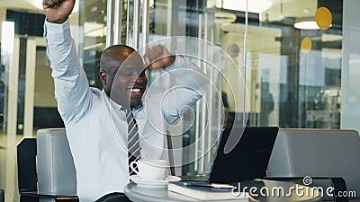 Homem de negócios afro-americano bem sucedido que usa o laptop que recebe a boa mensagem e tornado muito entusiasmado e a dança filme