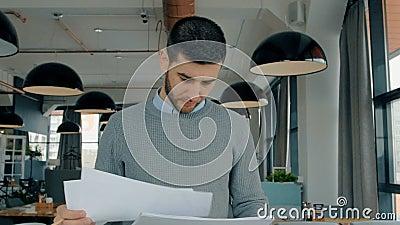 Homem de negócios americano que olha o projeto da partida, trabalhando na tabela no café moderno video estoque
