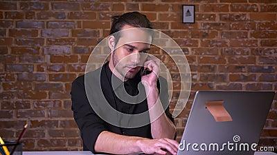 Homem de negócios caucasiano agradável que pendura no telefone e que olha o portátil concentrado quando se sentar na mesa de trab filme