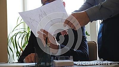 Homem de negócios considerável novo nos monóculos que guardam o papel com gráfico estatístico nas mãos e que dão a instrução para vídeos de arquivo