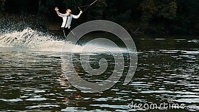 Homem de negócios extremo de terno com óculos de sol caminha em wakeboard e pulando em uma prancha de primavera em lago em câmera vídeos de arquivo