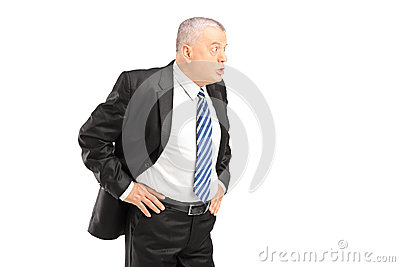 Homem de negócios maduro irritado na gritaria preta do terno