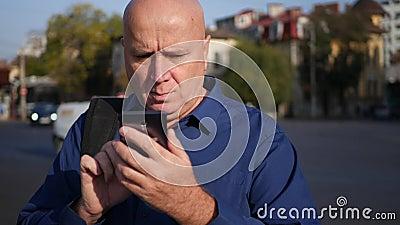 Homem de negócios preocupado Text Using Cellphone que anda na rua vídeos de arquivo