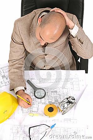 Homem de negócios que pensa com planos arquitectónicos