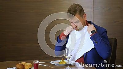 Homem de negócios que toma o guardanapo branco antes de comer durante o almoço no restaurante gourmet video estoque