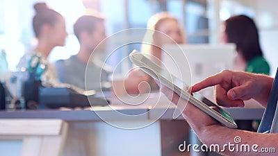 Homem de negócios que usa o tablet pc com seus colegas atrás dele
