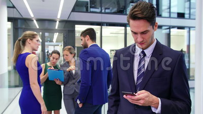 Homem de negócios que usa o telefone celular e o colega que discutem no fundo vídeos de arquivo
