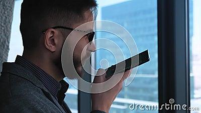Homem de negócios Smiles After Sending uma mensagem da voz Homem novo moderno elegante com um homem de negócios da barba que escr video estoque