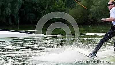 Homem de negócios surpreendido extremo em um terno com gravata e óculos de sol caminham em wakeboard em um lago filme