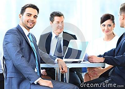 Homem de negócio maduro que sorri durante a reunião com colegas