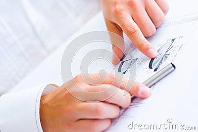 Homem de negócio que aponta às cartas e aos gráficos