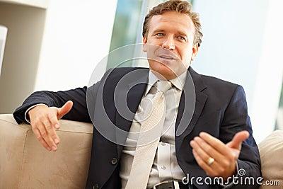 Homem de negócio que gesticula com mãos ao falar