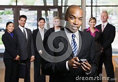 Homem de negócios africano que usa o telefone de pilha