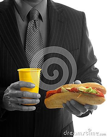 Homem de negócios que come o fast food da sucata