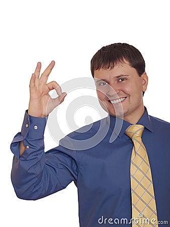 Homem de negócios que mostra o sinal e o sorriso APROVADOS