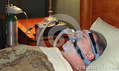 Homem de sono (perfil) com CPAP e oxigênio