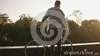 Homem de sorriso novo feliz nos óculos de sol que dão um ciclo uma bicicleta no parque ou no bulevar da manhã Movimento lento do  video estoque