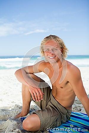 Homem de sorriso que senta-se em sua toalha de praia