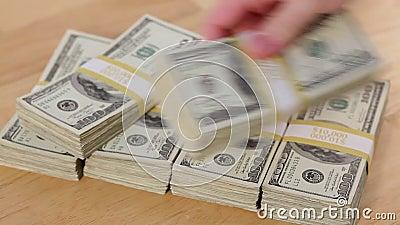 Homem deita pilhas de 100 Dólares em uma pirâmide sobre a mesa filme