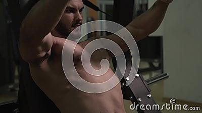 Homem desportivo atlético com o torso despido que dá certo em exercitar a máquina filme