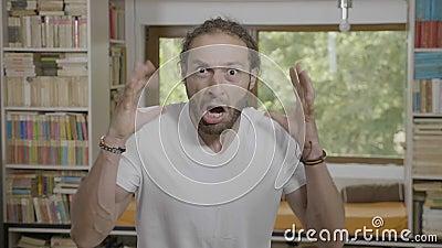 Homem do adolescente que grita de choque que olha aturdido com os olhos e a boca abertos largamente - video estoque