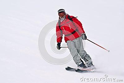 Homem do esquiador que funciona para baixo do recurso nevado mo do inverno